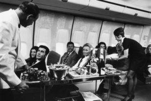 A steward and stewardess serving first-class passengers with drinks and refreshments on board a Boeing 747. (Photo by Fox Photos/Getty Images)